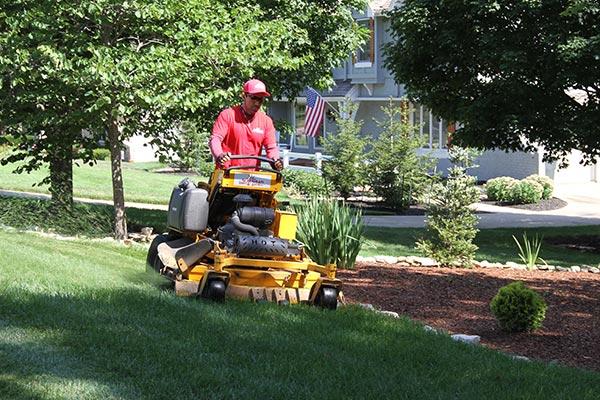 Suburban Lawn & Garden gardener mowing the lawn
